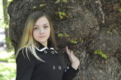 A girl and a big old tree. In the spring garden Stock Photo