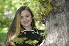 A girl and a big old tree. In the spring garden Stock Photos