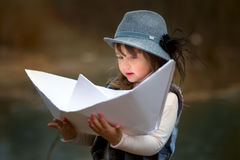 Girl with big paper boat. Near river at spring cloudy day stock images