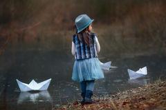 Girl with big paper boat. Near river at spring cloudy day royalty free stock photo