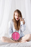 Girl with big pink clock the morning in bed Stock Photo