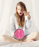 Girl with big pink clock the morning in bed Royalty Free Stock Image