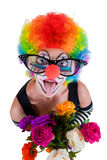 Girl in big red glasses and clown costume with a bouquet of flowers puts out the tongue looks up Stock Photography