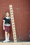 Girl with big ruler. Standing on wood background Royalty Free Stock Photography