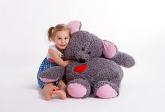 Girl with big soft toy mouse. Little baby girl with big soft toy mouse with heart Stock Photo