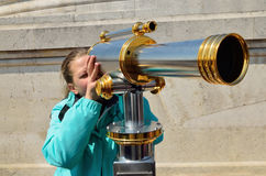 Girl with a big spyglass Stock Photo