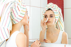 Girl with a big towel on her head looks in the mirror and rubs face with a cotton disk. Beautiful young girl with a big towel on her head looks in the mirror and Royalty Free Stock Photography