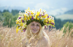 Girl in big wreath on a meadow Stock Photos