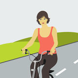Girl on bike. Girl rides a bike on the road Royalty Free Stock Photography