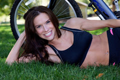 Sporty Female on Grass Mountain Bike Outdoors Royalty Free Stock Image
