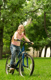 Girl on bike. Teen girl standing with a bicycle and stares into the distance Stock Image