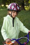 Girl with a Bike. Little girl in a helmet, keeping a bike Royalty Free Stock Photos