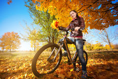 Girl with bike on a autumn leafs background Royalty Free Stock Photo