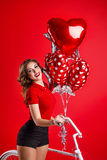 Girl with bike and balloons. Young attractive girl with bike and balloons in the shape of a heart. Romantic image Royalty Free Stock Photos