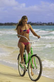 Girl on bike at beach texting Royalty Free Stock Image