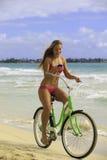 Girl on bike at beach texting Stock Photo