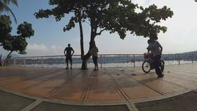 Girl bike couple stretch at lake-shore boardwalk. Silhouettes. San Pablo City, Laguna, Philippines - October 8, 2015: Girl bike couple stretch at lake-shore stock video
