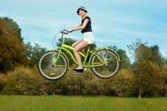 Girl on bike flies. Stock Photo
