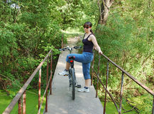 Girl with bike on footbridge Stock Photos