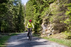 Girl on bike in forest at Ludrovska valley, Slovakia. Woman on mountain bike in forest at Ludrovska valley in Slovakia stock photo