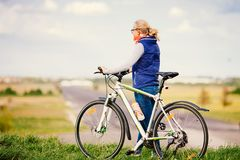 Girl with bike on hill Stock Image