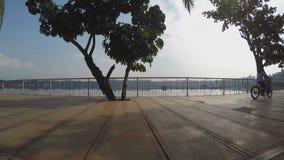 Girl bike at lake-shore boardwalk. Silhouettes. San Pablo City, Laguna, Philippines - October 8, 2015: Girl bike at lake-shore gazebo view deck boardwalk as stock video