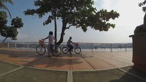 Girl bike at lake-shore boardwalk. Silhouettes. San Pablo City, Laguna, Philippines - October 8, 2015: Girl bike at lake-shore gazebo view deck boardwalk as stock footage