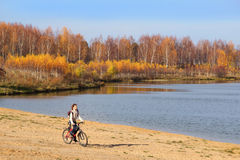 Girl with Bike on Lakeside Stock Images