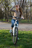 Girl on bike looking. Pretty girl on bicycle looking somewhere Stock Image