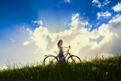 Girl with bike over sky Stock Images