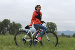 Girl on bike. Playing sports outdoors in the park Stock Image