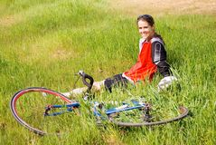 Girl after a bike ride. A girl resting in the grass after a bicycle ride stock photo