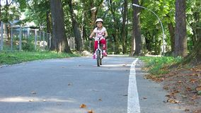 Girl on bike rides to the camera stock footage