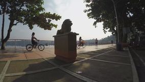 Girl bike run at lake-shore boardwalk. Silhouettes. San Pablo City, Laguna, Philippines - October 8, 2015: Girl bike run at lake-shore gazebo view deck boardwalk stock video footage