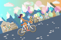 Girl on the bike. Sports girl is riding bike in colorful town with maintains Stock Photo