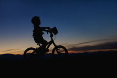 Girl on a Bike at Sunset Stock Images