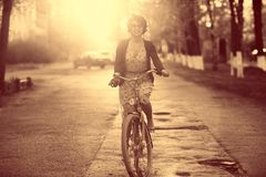 Girl on bike at sunset summer city Stock Photography