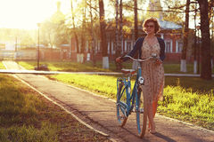 Girl with bike at sunset summer city Stock Photos