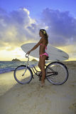 Girl with bike and surfboard Stock Photo