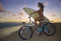 Girl with bike and surfboard Royalty Free Stock Image