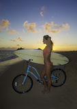 Girl with bike and surfboard Royalty Free Stock Images