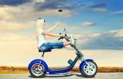 Girl biker riding a motorbike on an asphalt road and photographed. Hobbies to ride a scooter stock image