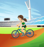 A girl biking at the field Stock Photography