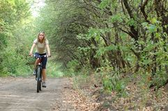 Girl biking in forest Royalty Free Stock Images