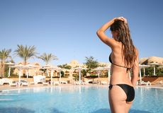 Girl  in bikini against resort pool Royalty Free Stock Images