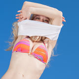 Girl in bikini on background of sky. Young blond woman in bikini undresses outdoors Stock Photography