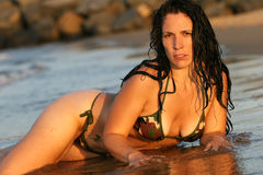 Girl in a Bikini on the Beach. A woman in a camouflage bikini laying in the surf on the beach Stock Images