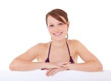 Girl in bikini behind white wall Stock Images