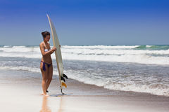 Girl in bikini costs on an ocean coast with a board for surf Royalty Free Stock Photography
