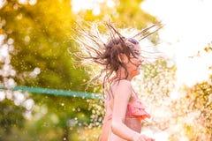 Girl in bikini dancing at the sprinkler, summer garden Royalty Free Stock Photography
